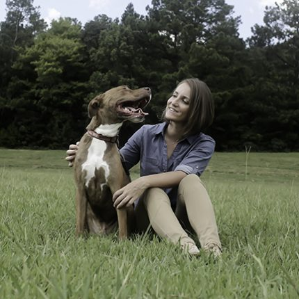 Dr. Cindy Johnson and her pit bull Loki sit in the grass